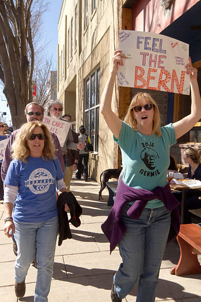 Feeling the Bern About Health Care Asheville, North Carolina, USA - February 28, 2016:  A crowd of Bernie Sanders rally supporters march holding a variety of signs about issues like health care during a campaign rally on February 28, 2016 in downtown Asheville, NC bernie sanders stock pictures, royalty-free photos & images