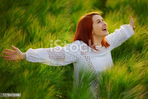 Redhead looking up feeling free and happy in the green wheat field