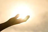 Woman's hand holding the Sun.