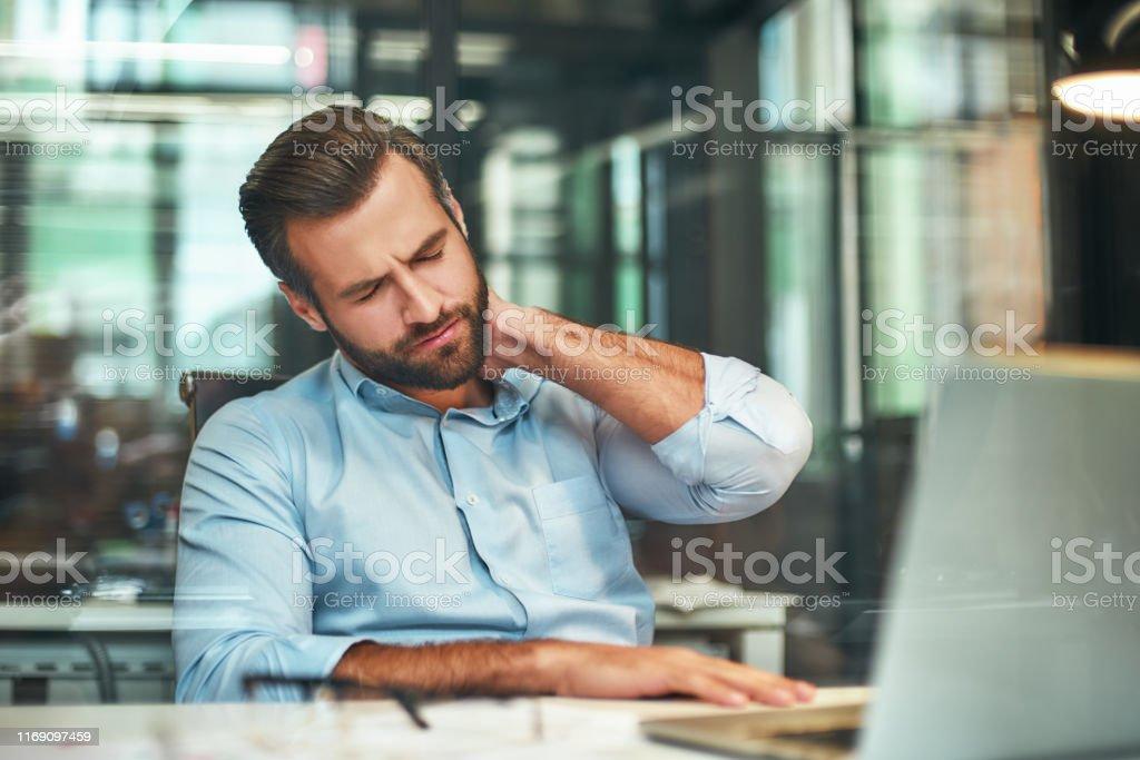 Sich müde fühlen. Junge bärtige Geschäftsmann in formaler Kleidung massieren seinen Hals, während im modernen Büro sitzen - Lizenzfrei Arbeiten Stock-Foto