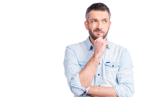 Frustrated young man in casual wear holding hand on chin and looking away while standing isolated on white background