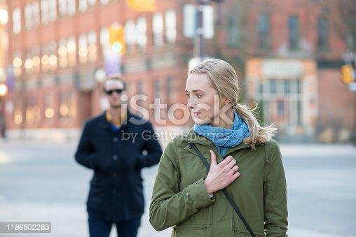 Scared young woman with blonde hair looking back over her shoulder at a stranger in a black trench coat that is following behind her downtown in an urban city.