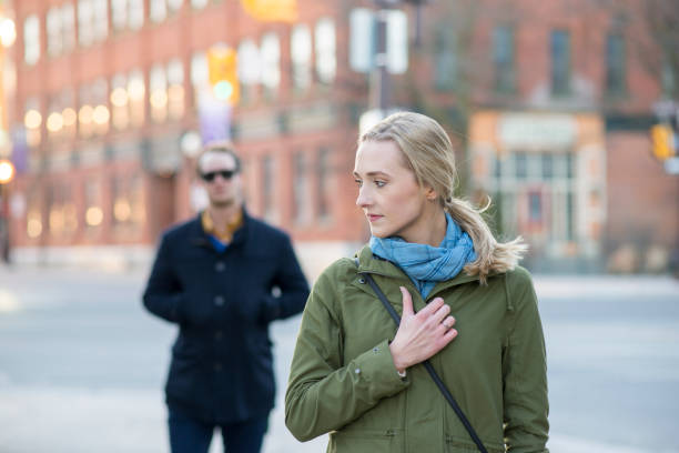 Feeling Unsafe When Walking Scared young woman with blonde hair looking back over her shoulder at a stranger in a black trench coat that is following behind her downtown in an urban city. stranger stock pictures, royalty-free photos & images