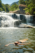 Full length shot of an unrecognizable woman swimming in a stream alone during a day outdoors