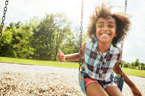Portrait of a young girl playing on a swing at the park