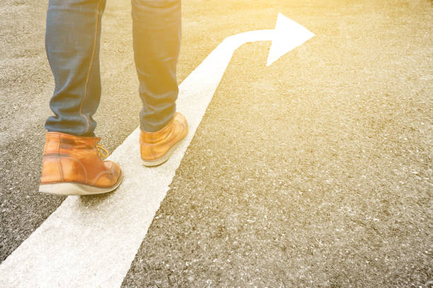 Feet and arrow on asphalt road background in starting line beginning idea. Selfie above view of hipster in boots or brown shoe standing on pathway. Top view. Moving forward, new start and success. stock photo