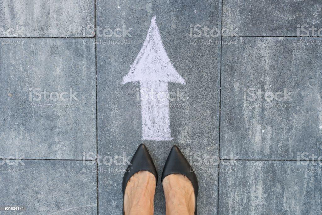 Feet and arrow on road. stock photo