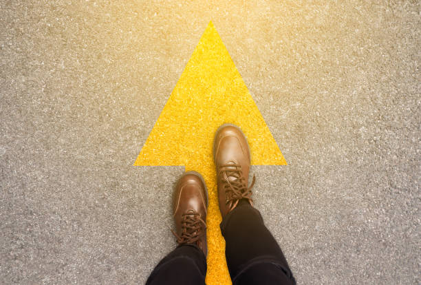 Feet and arrows on road background in starting line beginning idea. Top view. Woman in leather ankle boots on pathway with yellow direction arrow symbol. Moving forward, new start and success concept. stock photo