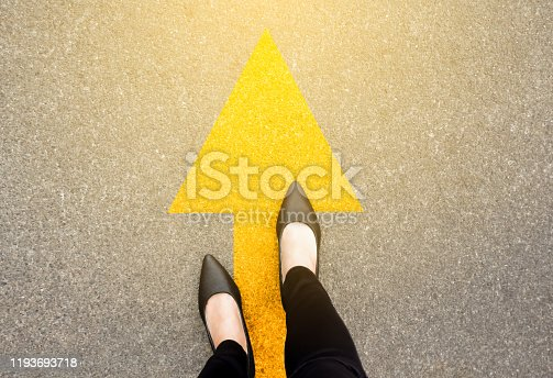 istock Feet and arrows on road background in starting line beginning idea. Top view. Business woman in black shoes on pathway with yellow direction arrow symbol. Moving forward, new start and success. 1193693718