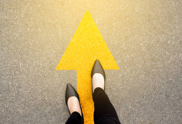 Feet and arrows on road background in starting line beginning idea. Top view. Business woman in black shoes on pathway with yellow direction arrow symbol. Moving forward, new start and success. stock photo