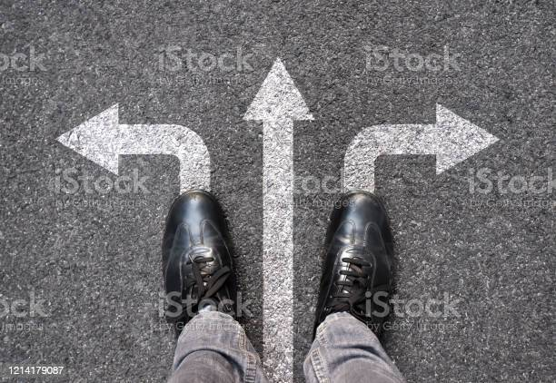 Photo of Feet and arrows on road background. Selfie feet above. Businessman standing on pathway with three direction arrows choice or move forward. Top view of business shoes walking. Motivation and growth.