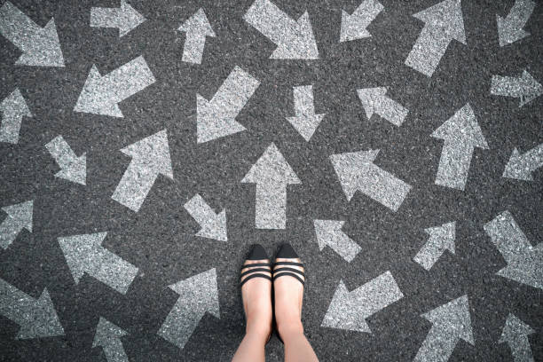 feet and arrows on road background. woman standing with many direction sign arrow choices in different ways, left and forward. - znak kierunku ruchu zdjęcia i obrazy z banku zdjęć