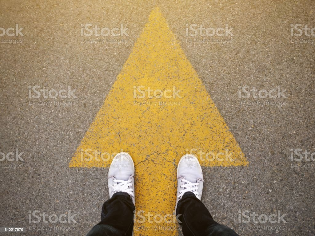 Feet and arrows on road stock photo