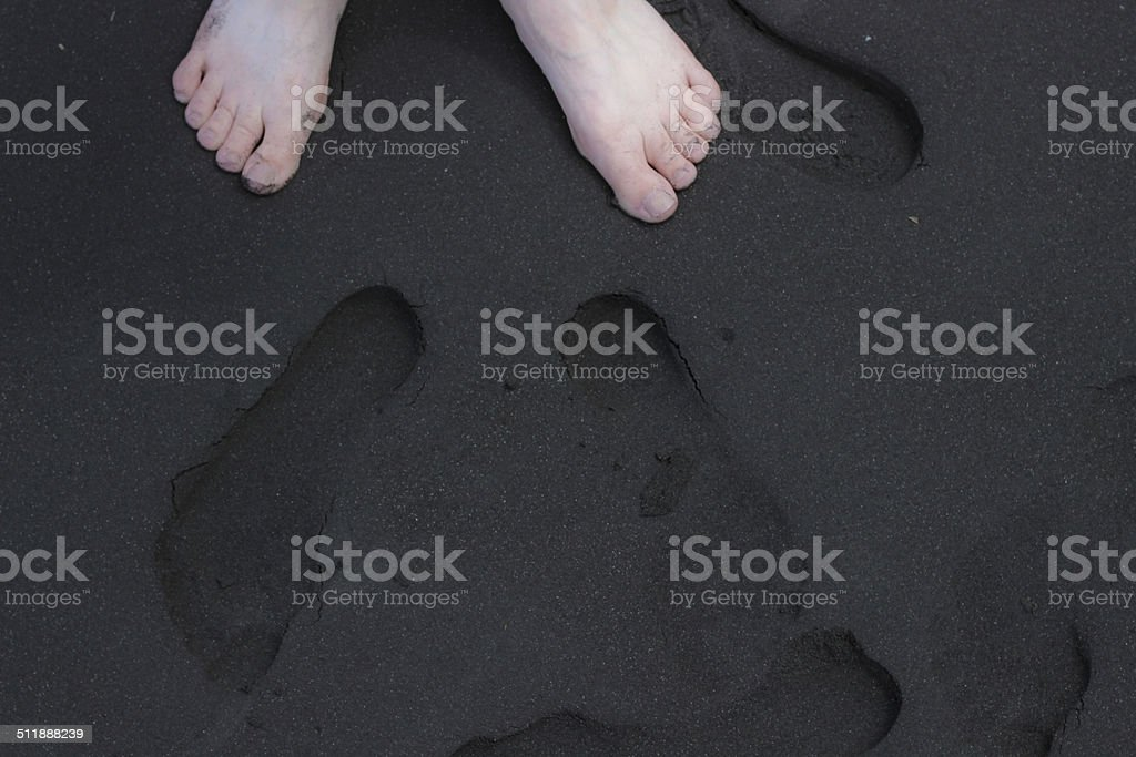 Feet and Footprints on Black Sand stock photo