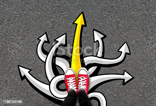 istock Feet and many arrows on road background. Pair of foot standing on concrete with color graffiti arrow sign 1166734196