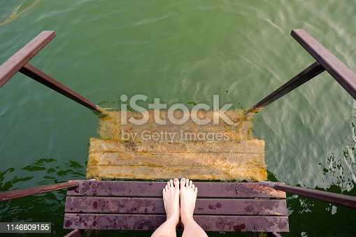 522909925 istock photo Feet and Purple Pedicure of Woman in Green Water, Top view. Beautiful Asian Young Female Body Legs and Barefoot on a Wooden Bridge Background. Cropped Image of People Foot Under Aqua Water on Summer. 1146609155