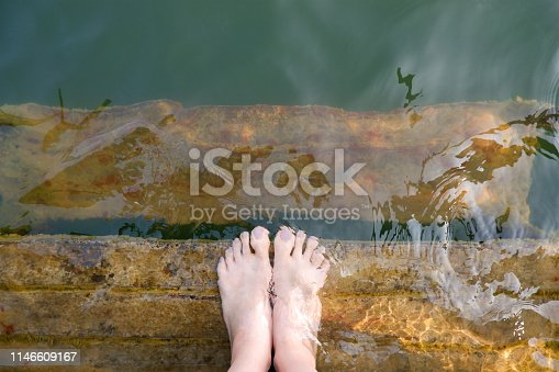 522909925 istock photo Feet and Purple Pedicure of Woman in Green Water, Top view. Beautiful Asian Young Female Body Legs and Barefoot on a Wooden Bridge Background. Cropped Image of People Foot Under Aqua Water on Summer. 1146609167