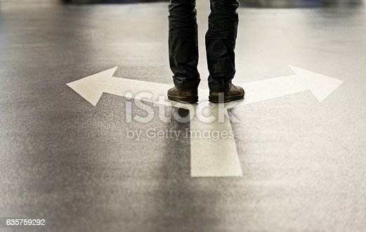istock Feet and two arrows painted on floor 635759292