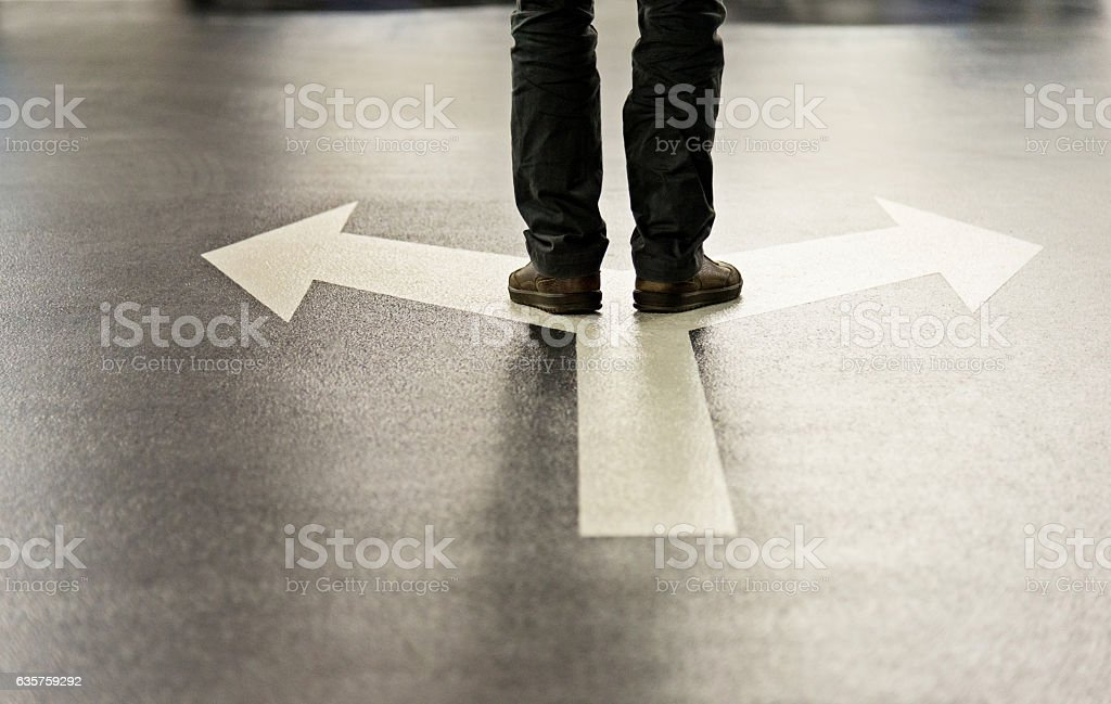 Feet and two arrows painted on floor stock photo