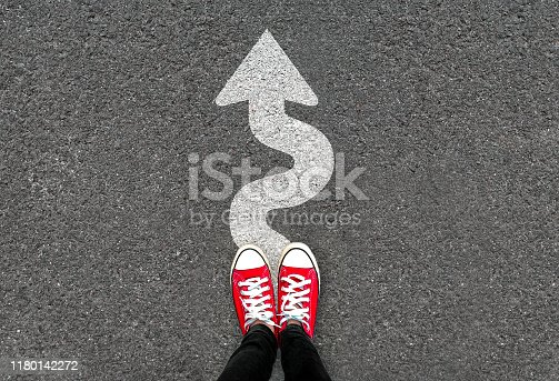 Feet and white arrow sign go straight on road background. Top view of woman. Forward movement and motivation idea concept. Selfie of foot and legs in red sneaker shoes on pavement floor from above.