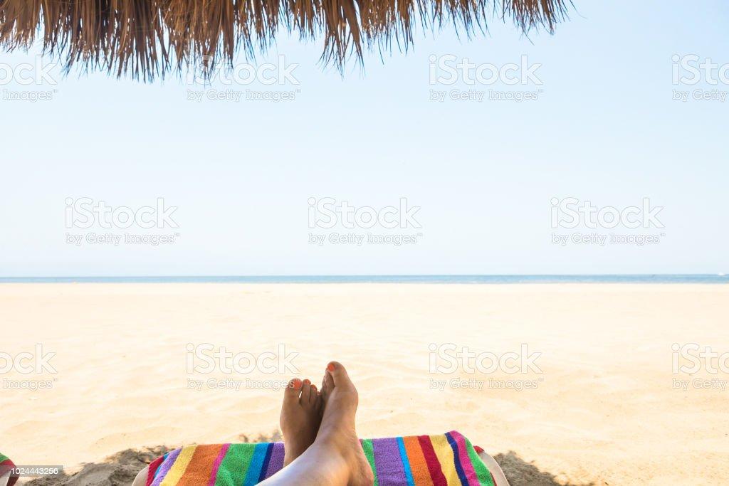 feet at the beach on a colorful beach towel stock photo
