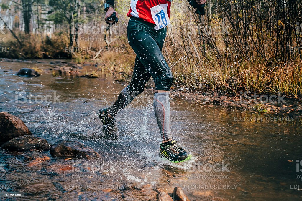 feet closeup male runner crossing river on rocks stock photo