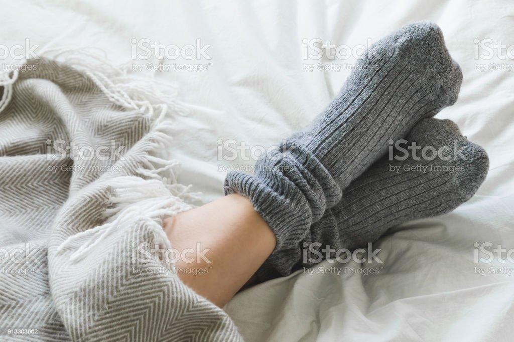 Pies cruzaron con calcetines gris en cama debajo de la manta - foto de stock