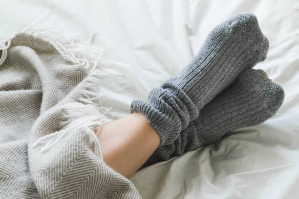 Feet crossed with gray socks on bed under blanket Pair of feet in gray socks on a bed under a cozy blanket. cozy stock pictures, royalty-free photos & images