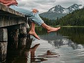 istock Feet dangling from lake pier 1283851025