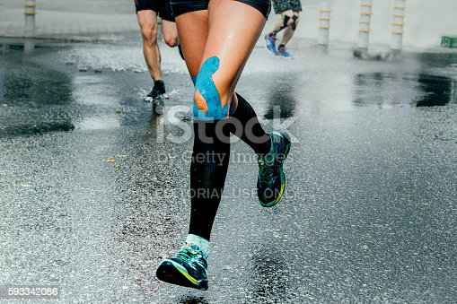 Ekaterinburg, Russia - August 7, 2016: feet girl runners in compression socks and taping on his knees, running on wet asphalt during Marathon Europe-Asia