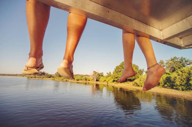 füße aus safariboot mit flip-flop hängen - flitterwochen flip flops stock-fotos und bilder