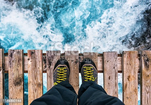 feet in hiking boots on the edge of an old wooden bridge