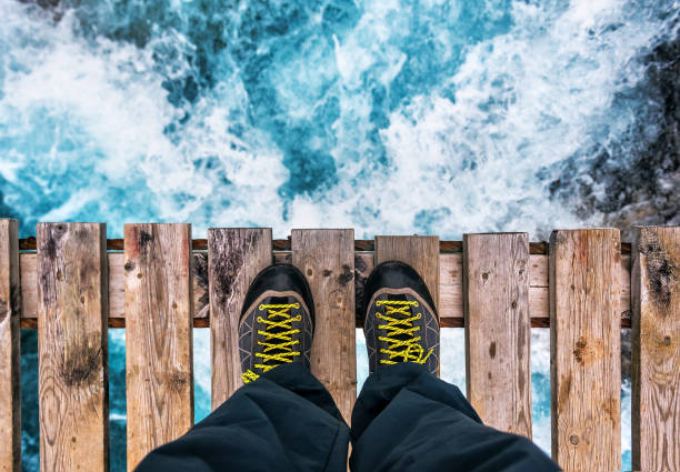 feet in boots on the edge of an old wooden bridge stock photo
