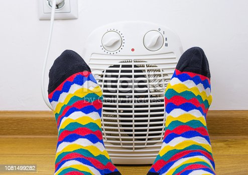 Feet in bright socks near electric fan heater at home. Close-up, selective focus.