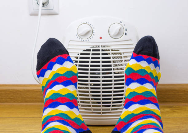 Feet in bright socks near electric fan heater at home. Close-up, selective focus. Feet in bright socks near electric fan heater at home. Close-up, selective focus. copy space stock pictures, royalty-free photos & images