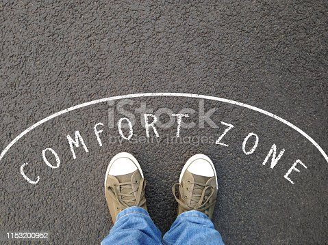 feet in canvas shoes standing inside comfort zone - foot selfie from personal perspective - chalk text on asphalt