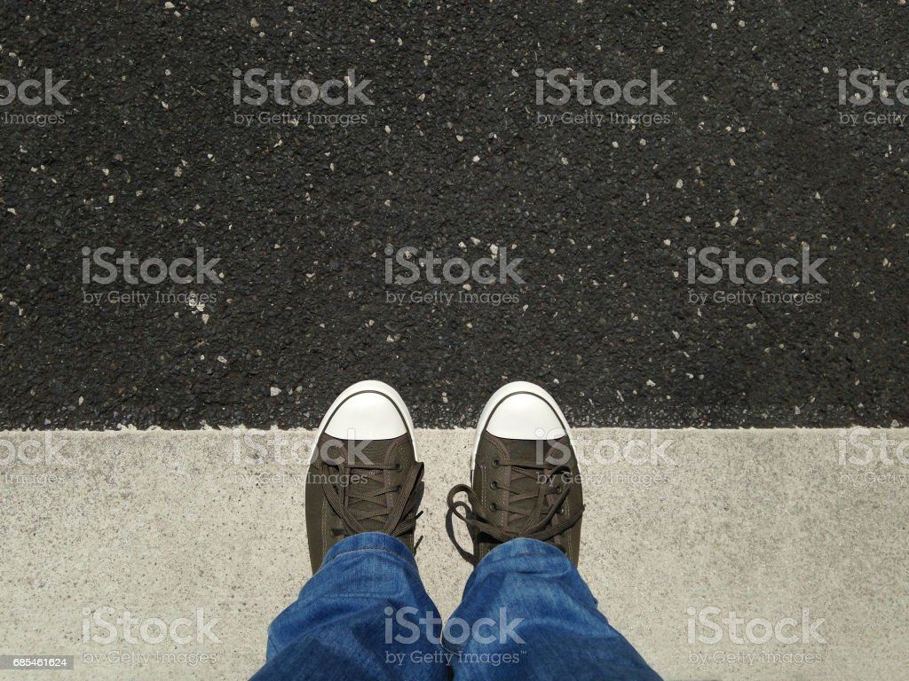 feet in canvas shoes standing on asphalt aligned with road markings foto de stock royalty-free