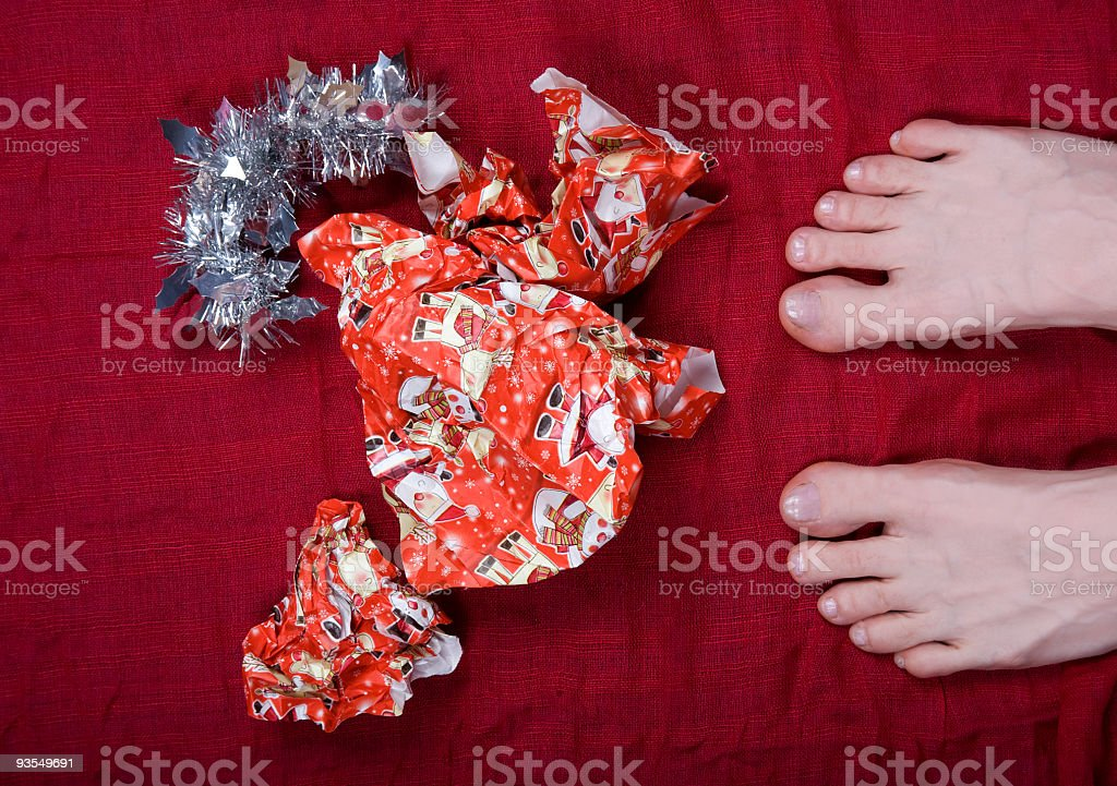 Feet in Christmas paper stock photo