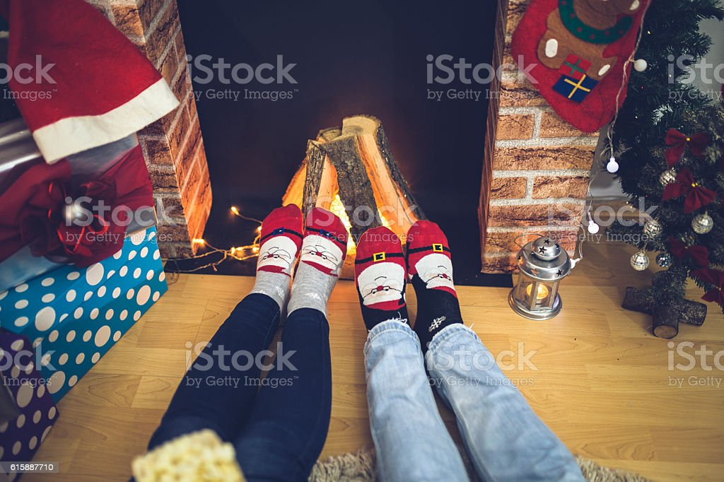 Feet in christmas socks warming by cozy fire stock photo