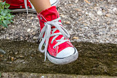 Little girl in red sneakers standing on the stairs