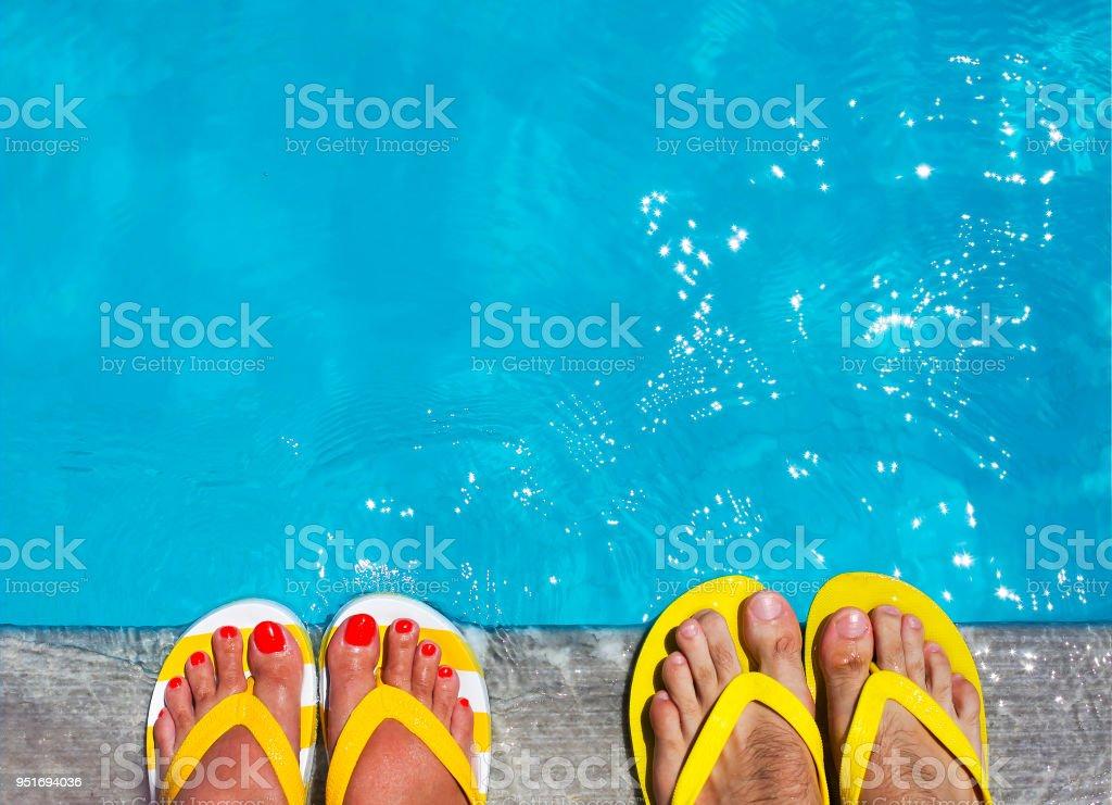 Feet in flip flops on stone background stock photo