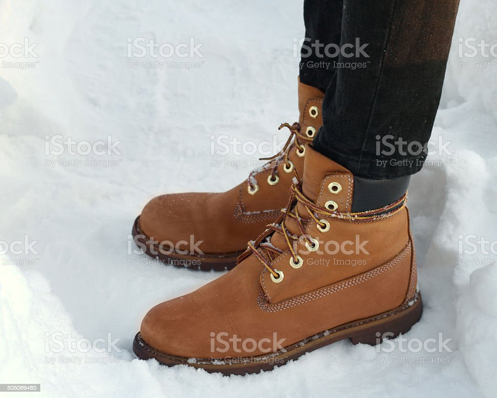 Feet in orange boots close up stock photo