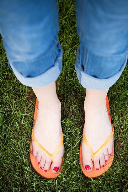 füße in orange flipflops - denim caprihosen stock-fotos und bilder