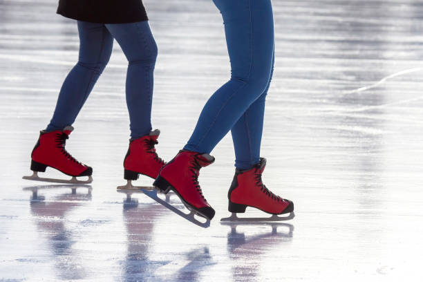feet in red skates on an ice rink. Hobbies and sports. Vacations and winter stock photo