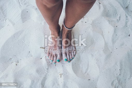 Two feet are in the sand. On the left joint she have yellow and green bracelet. Her nails are painted turquoise and toes are whole sticky with sand. On the sand we can see sunlight and shadow of this person.