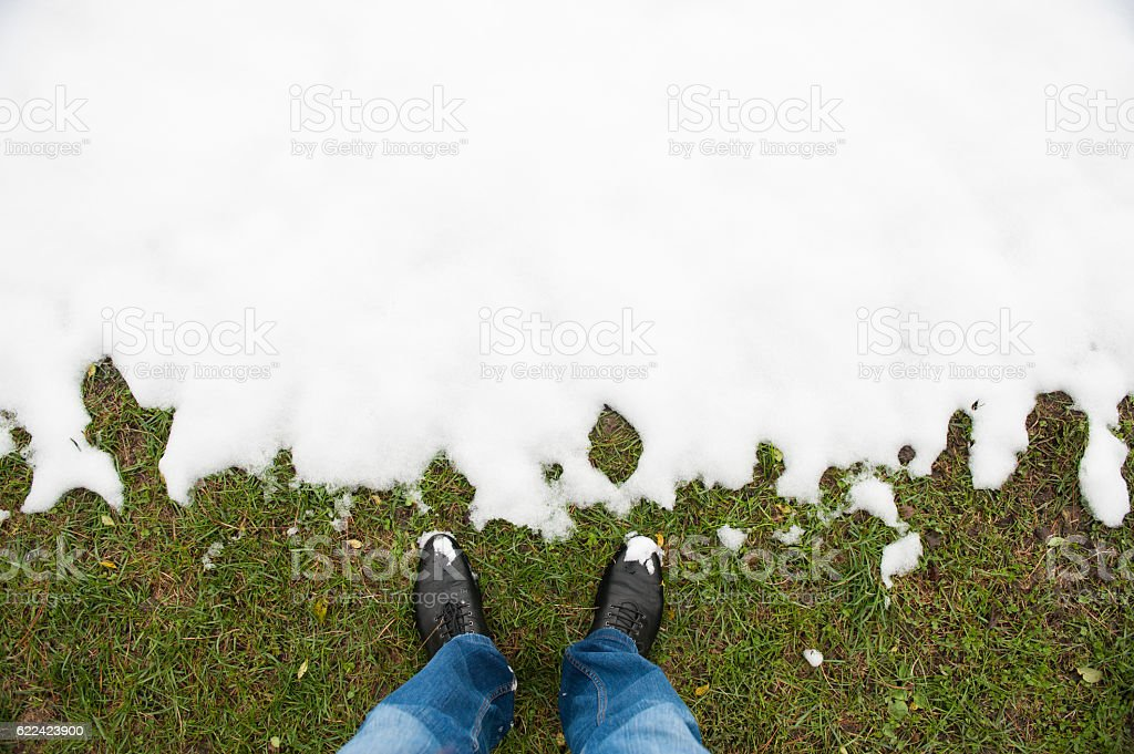 feet in   shoes   jeans standing on   grass before the snow stock photo