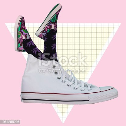 1014178170istockphoto Feet in shoes sticking out of a big shoe. Surrealism. 964255298