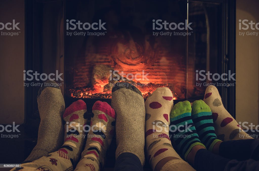 Feet in socks of all the family warming by fire. stock photo