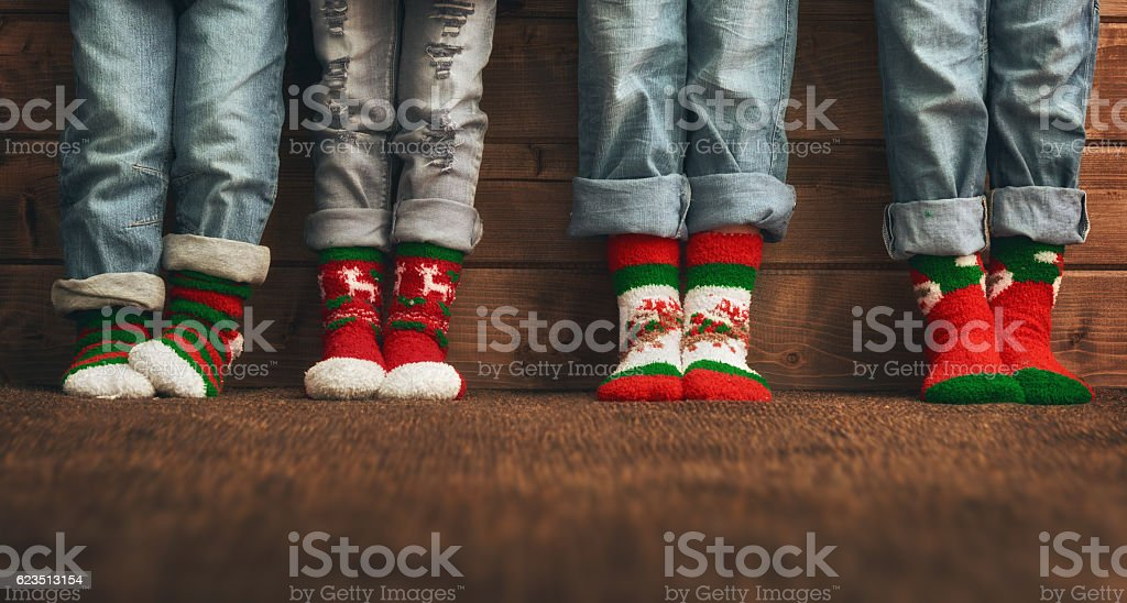 feet in socks with a Christmas ornament stock photo