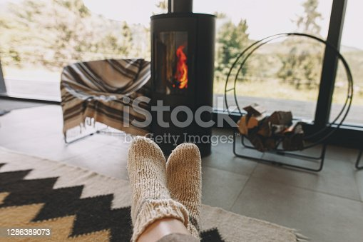 Feet in warm knitted woolen socks on background of modern black fireplace and big windows with view on mountains. Woman relaxing in comfortable home, cozy warm moments